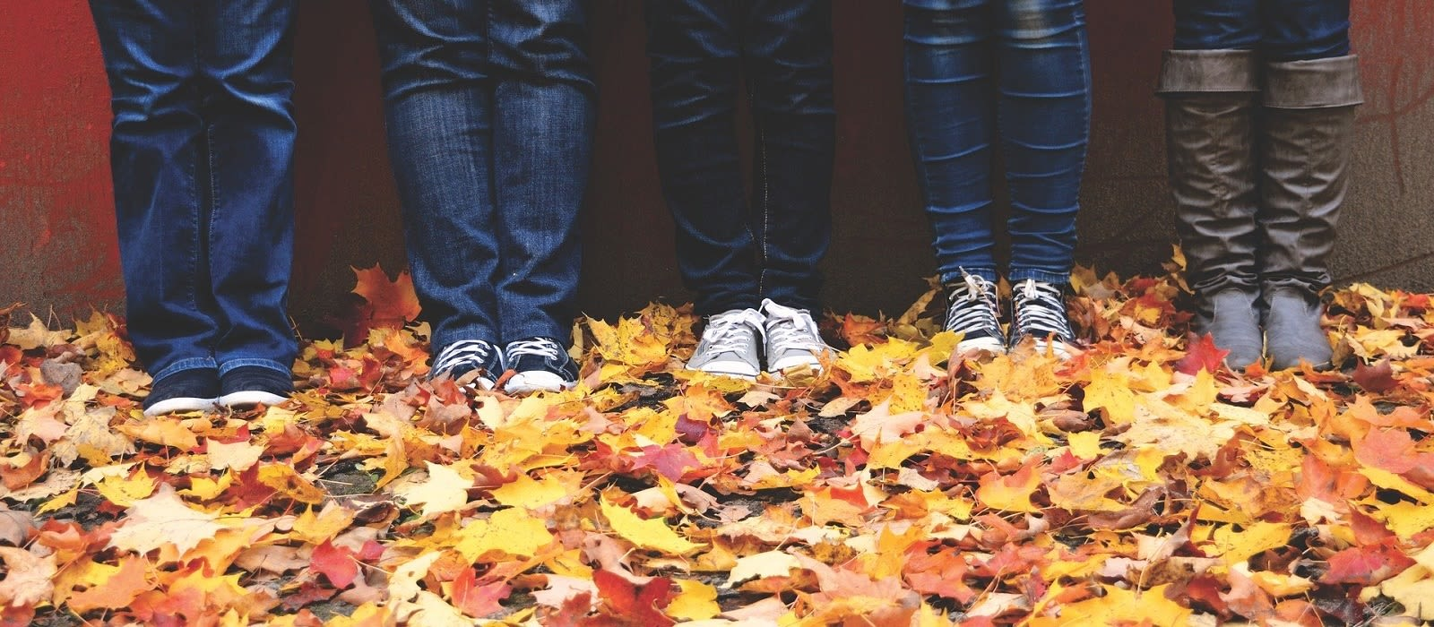 A photo of four peoples legs as they are standing in a pile of autumn leaves.