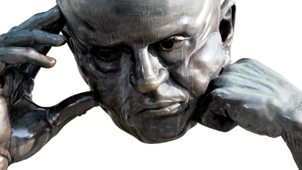 Bronze sculpture of a man in deep thought, with his head resting on his right hand whilst its in a ball and his left hand also touching his head.
