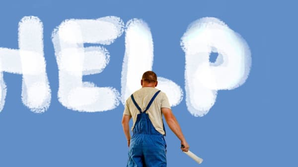 Help sign painted in white paint on a blue background by a man in a grey t-shirt and blue overalls.